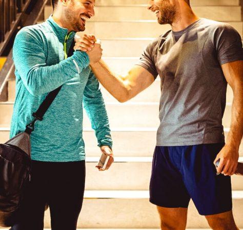 Happy handsome fit men friends talking, smiling after workout in gym