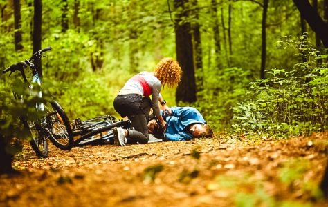 Young sportswoman leaning over male cyclist with broken leg on forest path and trying to understand what to do