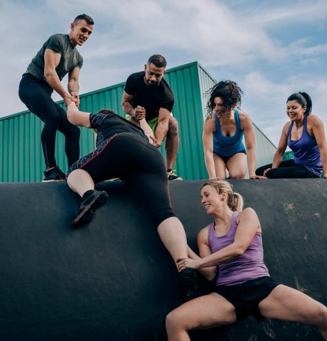 Group of participants in an obstacle course helping a teammate to climb a drum